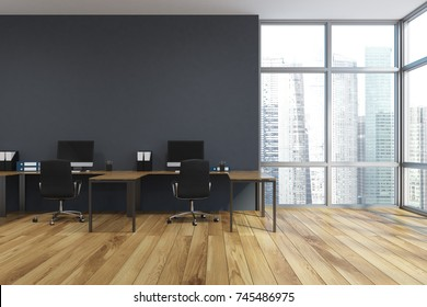 Open space office interior with gray walls, a wooden floor and large windows. A row of computer desks, desktops with blank screens. 3d rendering mock up