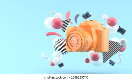 Orange camera surrounded by colorful balls on a blue background.-3d render.