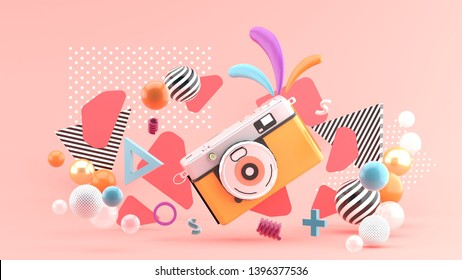 Orange camera surrounded by graphics and colorful balls on a pink background.-3d rendering.