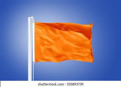 Orange flag flying in a stiff breeze against clear blue sky.
