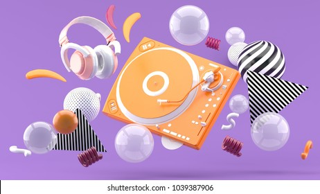 Orange turntable and orange headphones are among colorful balls on a purple background.-3d render