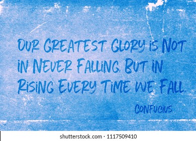 Our greatest glory is not in never falling, but in rising every time we fall - ancient Chinese philosopher Confucius quote printed on grunge blue paper