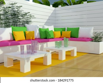 Outdoor patio seating area with big sofa and two tables.