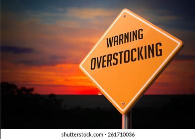 Overstocking on Warning Road Sign on Sunset Sky Background.