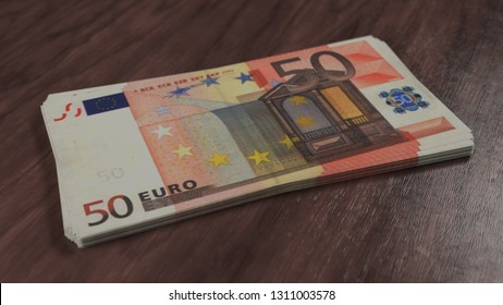 Pack of money. Fifty euro banknotes on the wooden floor. 50 european cash currency 3D illustration, depth of field.