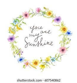 Painted watercolor composition of wild meadow flowers and grass with lettering. You are my sunshine. Wreath, frame, border, background. Greeting card, postcard