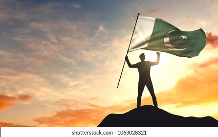 Pakistan flag being waved by a man celebrating success at the top of a mountain. 3D Rendering