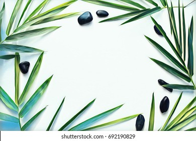 Palm leaf and pebble on blank background. Tropical plant ornament on table top view. Bamboo leaf with seashore pebble. Tropic frame flat lay. Clear fresh leaf background. Beauty or spa salon banner