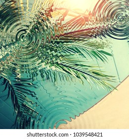 Palm trees and sunshade reflected in swimming pool water, photo with added digital effects. Vacation, relaxation and unwinding concept