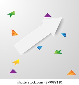 paper arrow surrounded by flying colored paper airplanes on a gray background