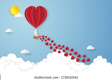 Paper art , cut and digital craft style of the lover in hot air balloons on blue sky and sunrise background as love , wedding, and valentine day concept.