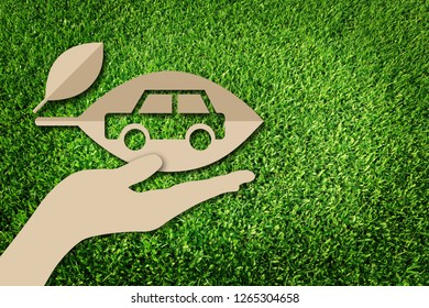 Paper cut of eco car concept on green grass background