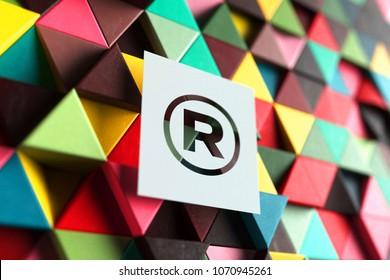 Paper ® Sign on the Triangle Red and Yellow Geometric Pattern. 3D Illustration of ® Sign Registered Trademark Symbol for Classic Backgrounds.