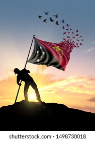 Papua New Guinea flag turn to birds while being planted by a man on a hill during sunrise.
