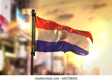Paraguay Flag Against City Blurred Background At Sunrise Backlight 3D Rendering