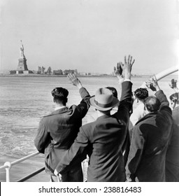 Part of a group of 171 illegal immigrants wave goodbye to Statue of Liberty from Coast Guard cutter that took them from Ellis Island to the Home Lines ship Argentina in Hoboken for deportation. 1952