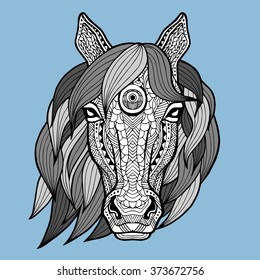 Patterned head of the horse on the blue background. African, indian design. It may be used for design of a t-shirt, bag, postcard, a poster and so on. Horse white black colors painted by hand.