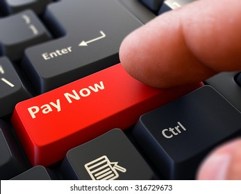 Pay Now Button. Male Finger Clicks on Red Button on Black Keyboard. Closeup View. Blurred Background.
