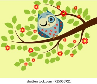Peeping. a blue owl in red flowers with one closed and one open eye sitting on a branch of a flowering tree