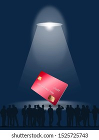 People stand around a modern credit card that is the center of attention and illuminated by a spotlight from above.