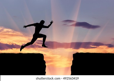 Perseverance and dedication. Runner athlete jumps over a precipice silhouette