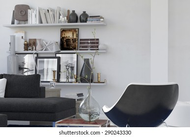 Personal cozy corner in a lounge interior with a modern armchair, comfortable couch and mementos on shelves on the wall. 3d Rendering.