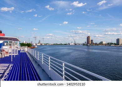 Perspective of top deck of cruise ship and view of industrial skyline of Norfolk along the Elizabeth River, Virginia, USA, with digital oil-painting effect, for coastal, travel, and maritime themes