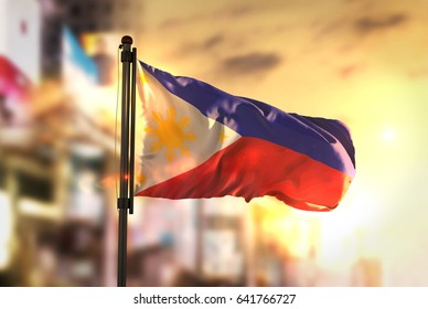 Philippines Flag Against City Blurred Background At Sunrise Backlight 3D Rendering