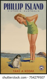 Phillip Island, Victoria, Australia. Take a Kodak. 1930s travel poster for Victorian Railways Australia of a bathing beauty on a beach with a penguin.