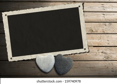 Photo Frame on Wooden Boardwalk with Sand / Aged and romantic photo frame with two stone hearts on wooden floor with sand