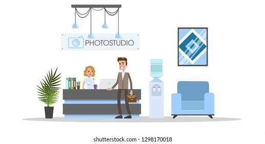 Photostudio interior with people and equipment on white.