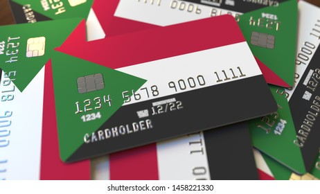 Pile of credit cards with flag of Sudan. Sudanese banking system conceptual 3D rendering