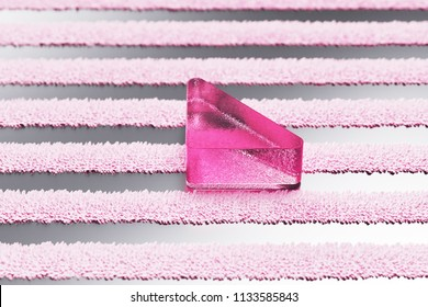 Pink Caret Down Glass Icon on Metalllic Striped Background. 3D Illustration of Pink Arrow, Caret, Down, Download Icon Set With Stripe Metalllic Pattern.