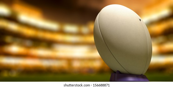 A plain white textured rugby ball on a blue kicking tee in a stadium at night