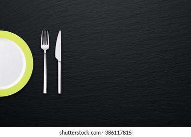 Plate  with fork and knife on gray slate textured background