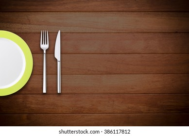 Plate with fork and knife on wooden background