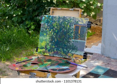 Plein air in sunny landscape nature. Canvas on sketchpad, a palette with used paints. Drawing in yard.