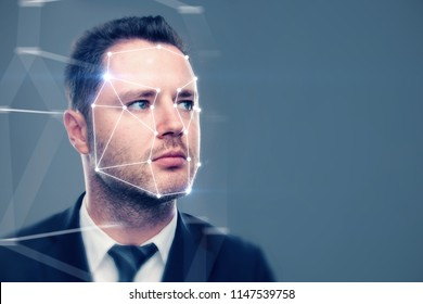 Portrait of attractive young businessman with facial recognition system. Authentication and scanning concept
