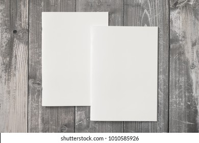 Portrait Magazines with blank soft cover on wooden desk. 3d Illustration for your presentation.