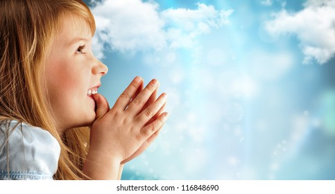 Portrait of young smiling praying girl in blue dress against sky background. Lots of copyspace