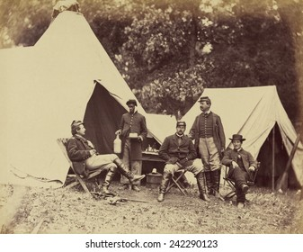 Posing for the camera, a White officer faces his young Black servant, who is holding bottle and cake. Displays the good life available in the Union Camps. November 1862 photo by Alexander Gardner.