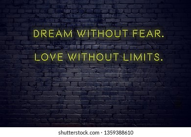 Positive inspiring quote on neon sign against brick wall dream without fear love without limits.