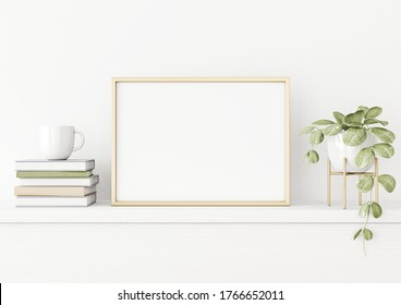 Poster mockup with horizontal gold metal frame on the table with green plant in pot, books, cup and trendy interior decoration on empty white wall background. A4, A3 size. 3D rendering, illustration.