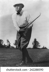 President Warren G. Harding (1865-1923), swinging golf club.