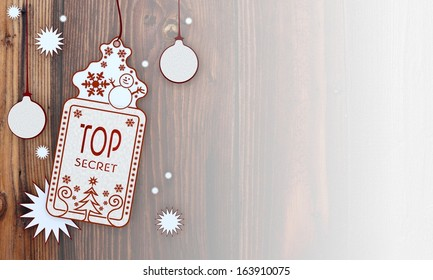 private illustration of a christmas card with top secret label in front of a wooden background with gradient to white