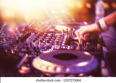 Professional club dj playing music on party in night club.Female disc jockey plays musical tracks on concert stage.Motion blur effect & bright lights