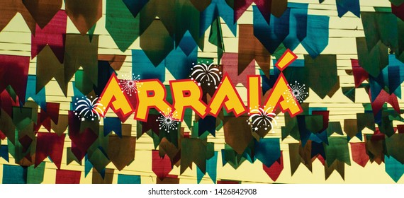"Promotional banner with the word ""ARRAIA"", about brazilian june party, in center of composition. Text space in both sides. On background, multicolored paper flags"