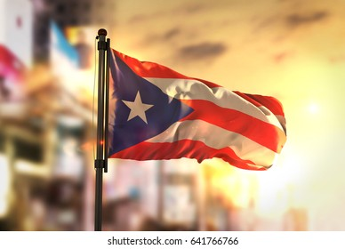 Puerto Rico Flag Against City Blurred Background At Sunrise Backlight 3D Rendering