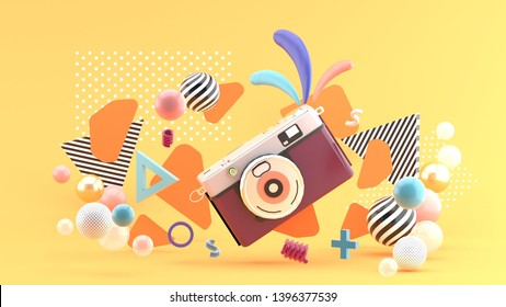 Purple camera surrounded by graphics and colorful balls on an orange background.-3d rendering.