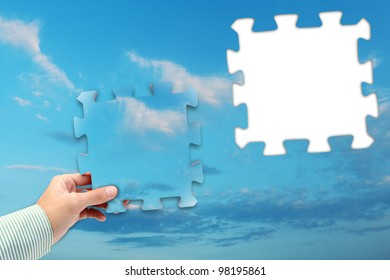 puzzle in hand on blue sky background